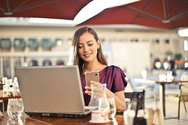 Woman using laptop and looking at her smartphone
